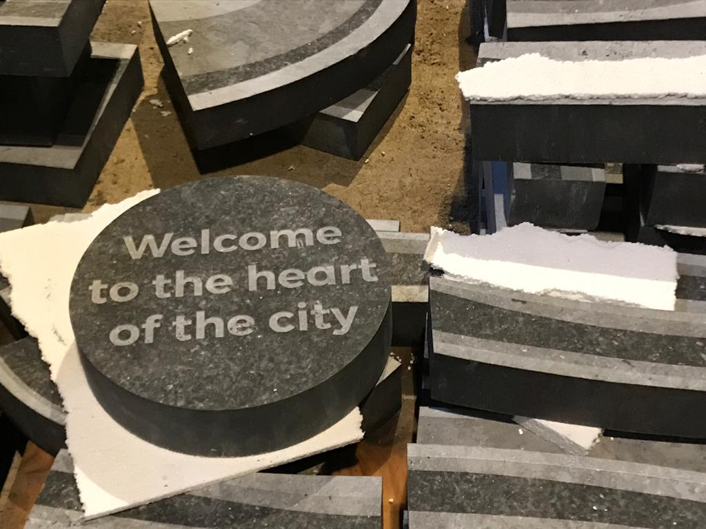 A stone roundel reading: 'Welcome to the heart of the city'