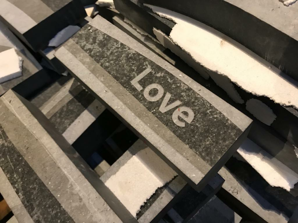 A stone panel reading: 'Love'