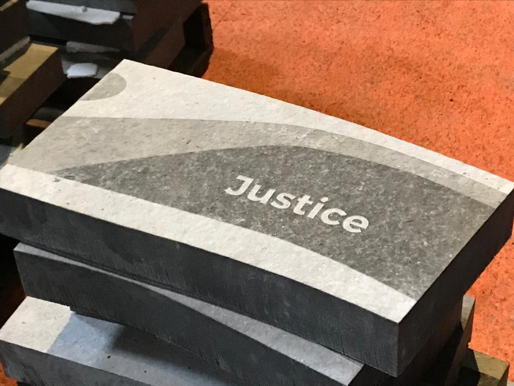 A stone panel reading: 'Justice'